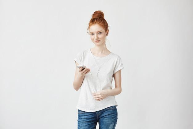 Ruda kobieta w słuchawkach uśmiechnięty, trzymając telefon.