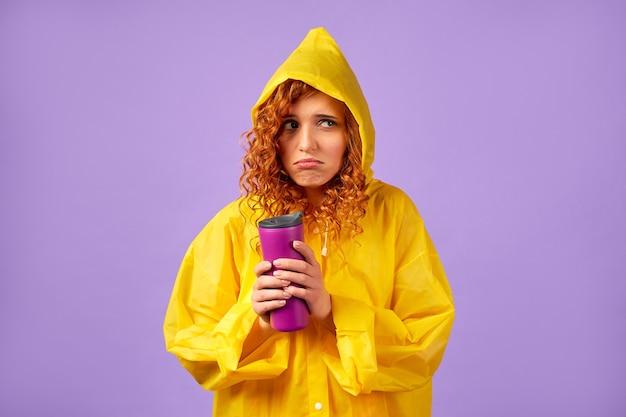 Ruda kobieta w żółtym płaszczu przeciwdeszczowym i kubku termicznym na fioletowym tle