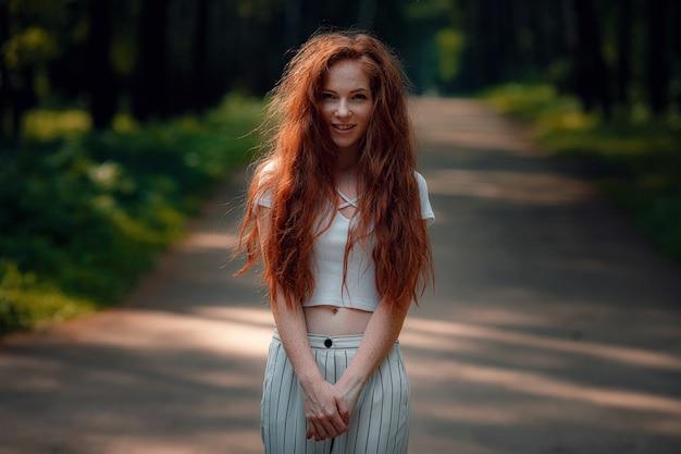 Ruda kobieta w zwykłych ubraniach na drodze na tle lasu