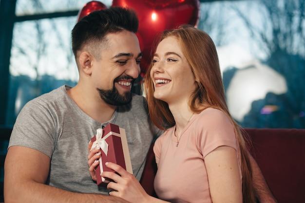 Ruda kobieta z piegami otrzymuje prezent od swojego kochanka podczas randki w domu