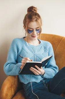 Ruda kobieta z piegami pisząca coś w książce i siedząca w fotelu nosi hydrożelowe opaski na oczy