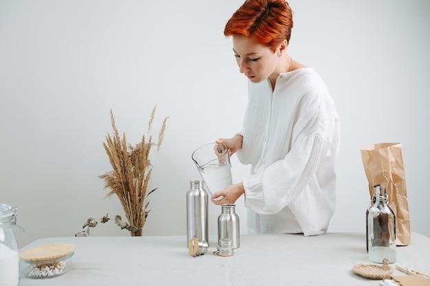 Ruda krótkowłosa kobieta nalewa wodę do metalowego termosu z dzbanka. na środku stołu.
