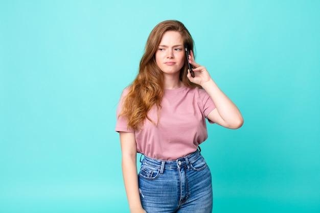 Ruda ładna kobieta czuje się smutna, zdenerwowana lub zła i patrzy w bok i używa smartfona