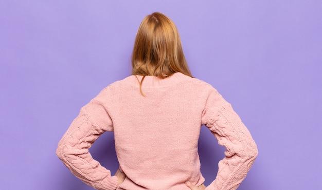 Ruda ładna kobieta czuje się zagubiona lub pełna lub ma wątpliwości i pytania, zastanawia się, z rękami na biodrach, widok z tyłu