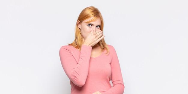 Ruda ładna kobieta czuje się zniesmaczona, trzymając nos, aby uniknąć nieprzyjemnego zapachu