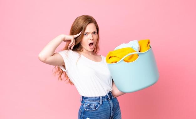 Ruda ładna kobieta wyglądająca na zaskoczoną, realizującą nową myśl, pomysł lub koncepcję i trzymającą kosz do prania z ubraniami