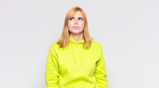 Ruda ładna kobieta wyglądająca na zdziwioną i zdezorientowaną, zastanawiającą się lub próbującą rozwiązać problem lub myśleć