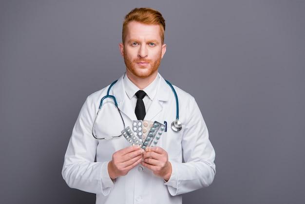 Ruda lekarz w fartuchu laboratoryjnym pozuje na szarej ścianie