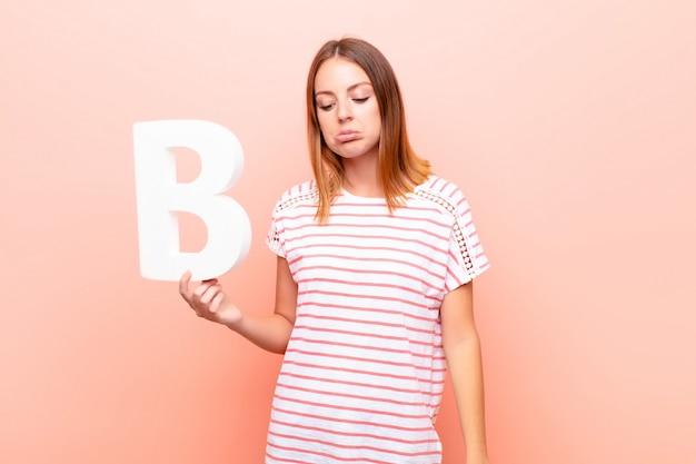 Ruda młoda dziewczyna w koszulce z literą b.