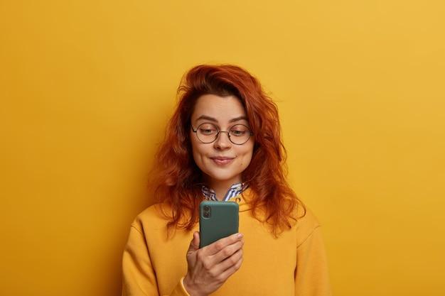 Ruda młoda kobieta trzyma telefon komórkowy, czyta powiadomienie, nosi okrągłe okulary i żółty sweter