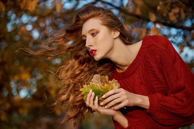 Ruda młoda kobieta w czerwonym swetrze spacery po parku. jesienny portret urody modnej rudowłosej kobiety o zachodzie słońca