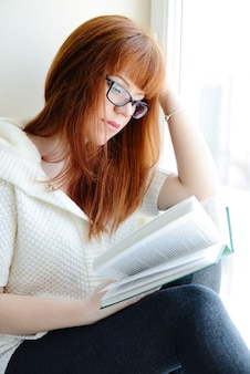 Ruda młoda kobieta z książką w pobliżu okna