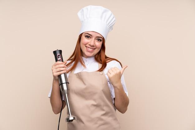 Ruda nastolatka kobieta za pomocą blendera wskazującego na bok, aby przedstawić produkt