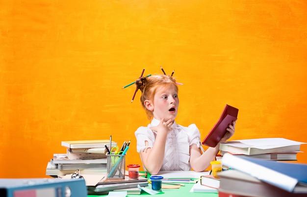 Ruda nastolatka z dużą ilością książek w domu