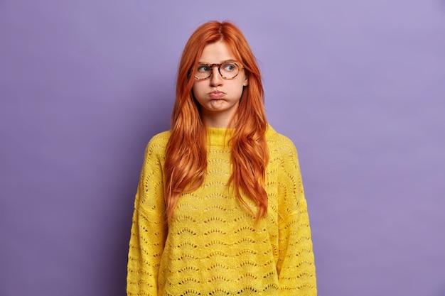 Ruda obrażona młoda kobieta dmucha w policzki i robi niezadowolony grymas trzyma powietrze ma nastrojowy wyraz nosi żółty sweter niezadowolony z okropnej sytuacji zdarzyła się pokazuje zły charakter