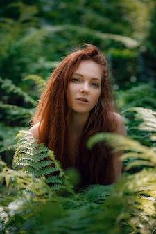 Ruda piękna kobieta bez ubrania pozuje za krzakami w lesie z pięknym światłem słonecznym