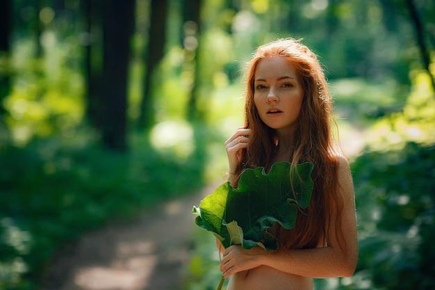Ruda piękna kobieta trzymająca duży urlop nad klatką piersiową bez ubrania pod spodem w lesie