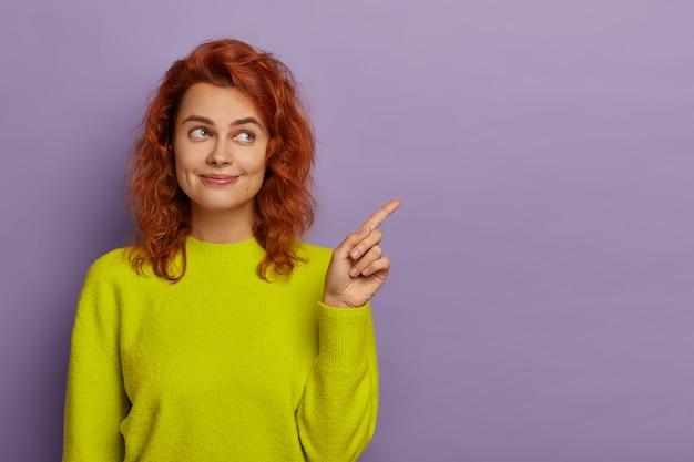 Ruda piękna kobieta wskazuje palcem wskazującym na bok, ubrana w jasnożółty sweter, demonstruje miejsce kopiowania treści reklamowych lub promocyjnych, sugeruje użycie pustego miejsca na informacje