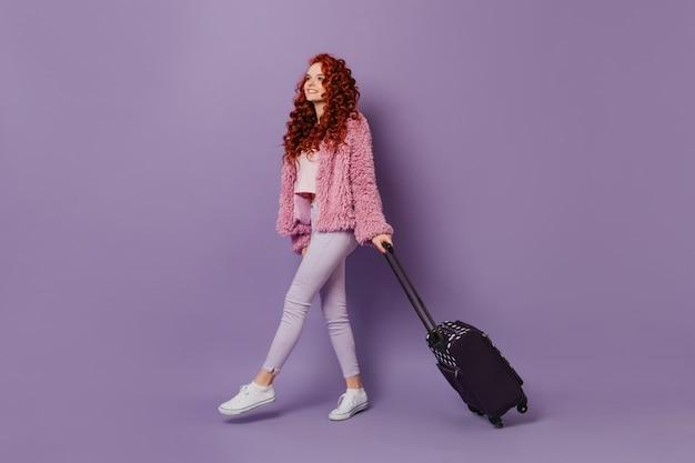 Ruda podróżniczka w różowym płaszczu i białych dżinsach ma walizkę na fioletowej przestrzeni.
