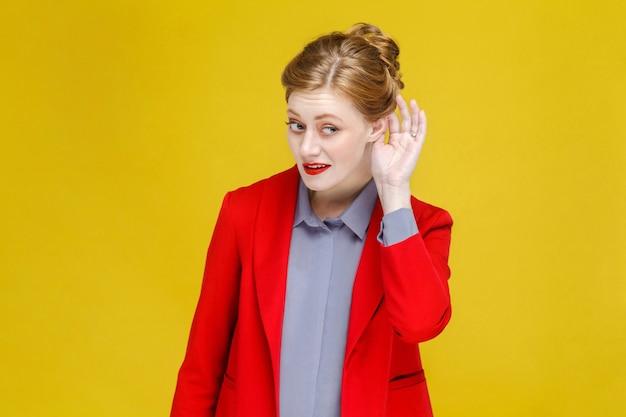 Ruda ruda kobieta w czerwonym garniturze słucha sekretu s