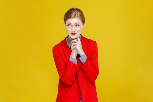 Ruda ruda kobieta w czerwonym garniturze życzy i marzy