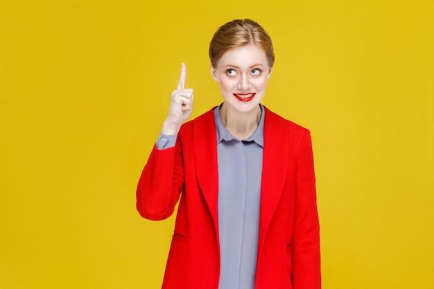 Ruda rudowłosa biznesowa kobieta w czerwonym garniturze ma dobry pomysł na plan