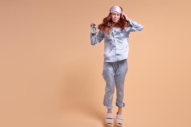 Ruda śpiąca kobieta na białym tle beżowym w piżamie, trzymając zegar z zdenerwowanym rozczarowanym wyrazem twarzy, pozowanie. zdezorientowana pani z maską na czole, kobieta nie ma dość snu