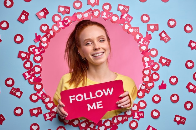 Ruda suczka trzymająca znak follow me, proś o większą aktywność w internecie, wysyłaj polubienia i wiadomości