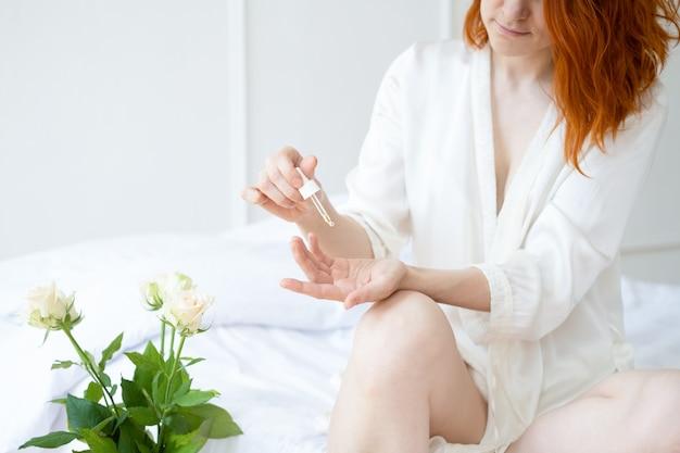 Ruda uśmiechnięta kobieta w średnim wieku w jedwabnej szacie z olejkiem kosmetycznym do rąk i ciała w jasnym pokoju