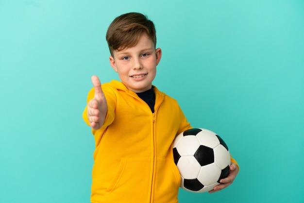 Rude dziecko gra w piłkę nożną na białym tle na niebieskim tle, ściskając ręce, aby zamknąć dobrą ofertę