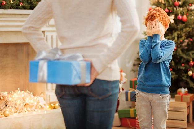 Rude dziecko w swobodnym stroju, zamykające oczy rękami, stojąc w postaci kochającej matki chowającej za plecami prezent gwiazdkowy.