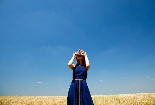 Rude dziewczyny na wiosnę pole z kamerą retro.