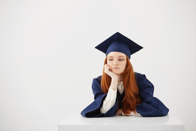 Rude kobiety absolwentka w płaszczu myślenia siedzi.