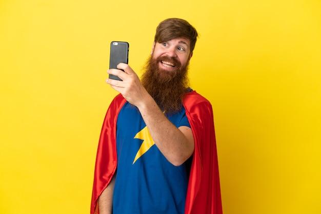 Rude super hero mężczyzna na białym tle na żółtym tle robi selfie