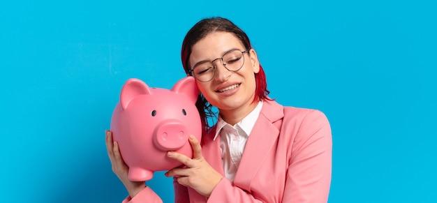 Rude włosy fajna kobieta trzyma różową skarbonkę
