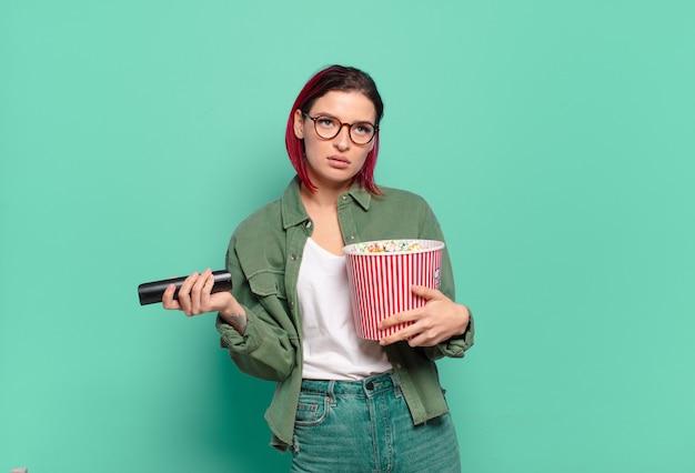 Rude włosy fajna kobieta z popcornami i pilotem do telewizora
