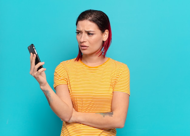 Rude włosy fajna kobieta za pomocą inteligentnego telefonu.