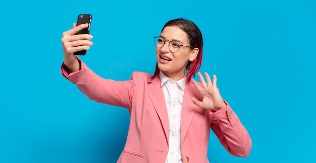 Rude włosy fajna kobieta ze smartfonem