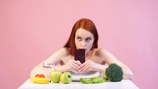 Rudowłosa anoreksyjna dziewczyna łapczywie je czekoladę. zaburzenia odżywiania. anoreksja