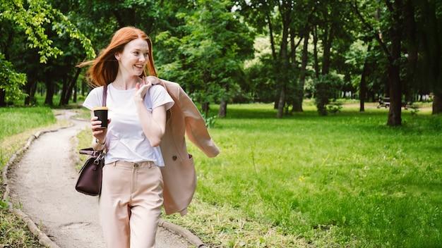 Rudowłosa biznesowa kobieta cieszy się wakacjami w parku