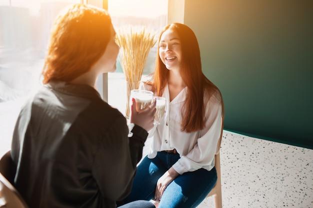 Rudowłosa dwie młode kobiety rozmawiają i piją kawę. modelki loughing w kawiarni