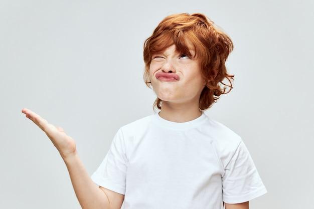 Rudowłosa dziecko z grymasem twarzy gestykuluje ręką biały t-shirt szare tło studio copy space
