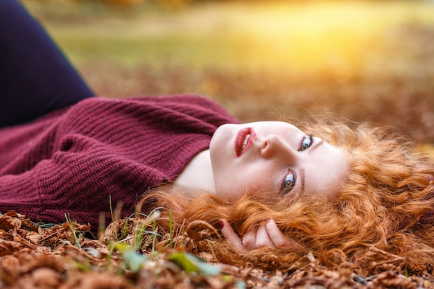 Rudowłosa dziewczyna leży w opadłych żółtych liściach