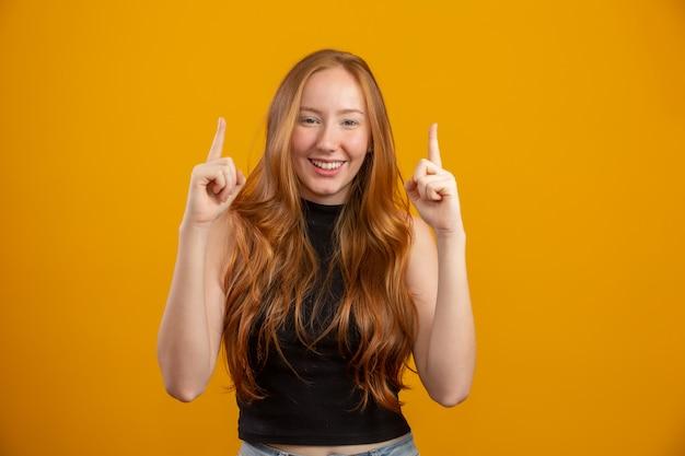 Rudowłosa dziewczyna na żółtej ścianie oferuje możliwości wskazania palcem na wolne miejsce na kopię treści reklamowej.