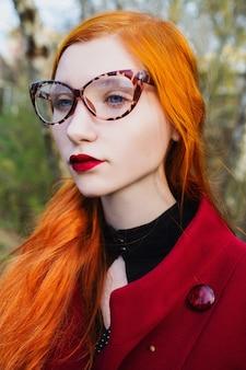 Rudowłosa dziewczyna o niebieskich oczach i bladej skórze w czerwonym płaszczu. kobieta w lampart okulary patrząc od hotelu. portret profil. biedronka bozhya. czerwony przycisk. czerwone usta.
