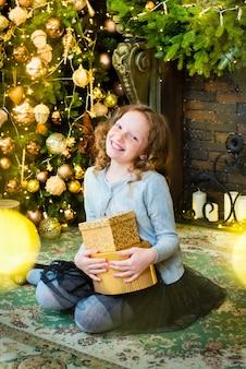 Rudowłosa dziewczyna otwiera prezent obok choinki