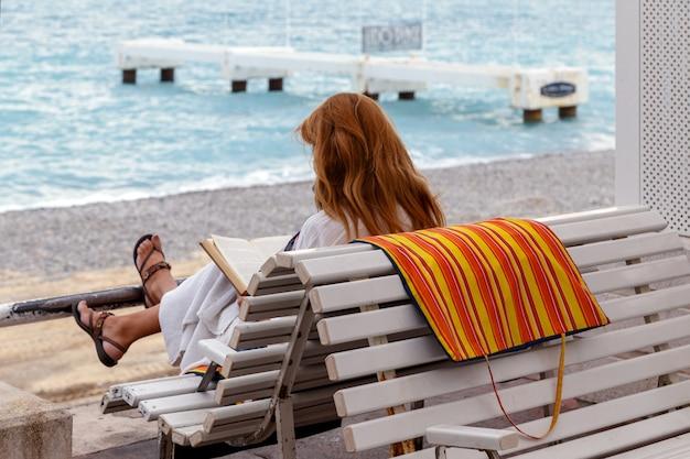 Rudowłosa dziewczyna siedzi na ławce i czyta książkę na plaży widok z tyłu