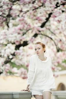 Rudowłosa dziewczyna stoi na drzewie różowy kwiat