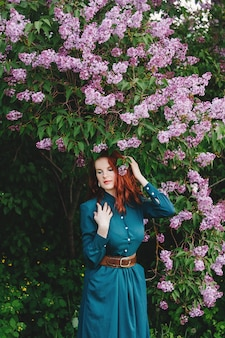 Rudowłosa dziewczyna stoi w pobliżu bzu