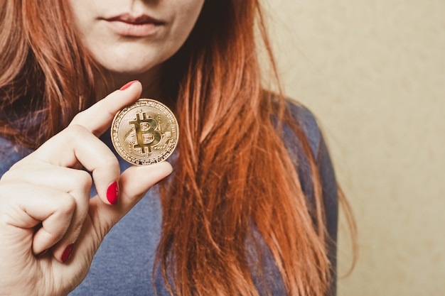 Rudowłosa dziewczyna trzyma w dłoni złotą monetę bitcoin
